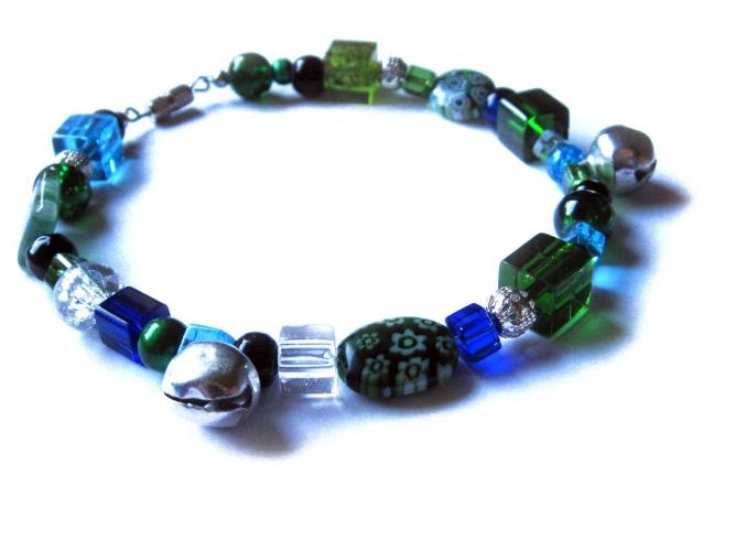 Grünes Fusskettchen mit silberfarbenen Elementen und Glöckchen